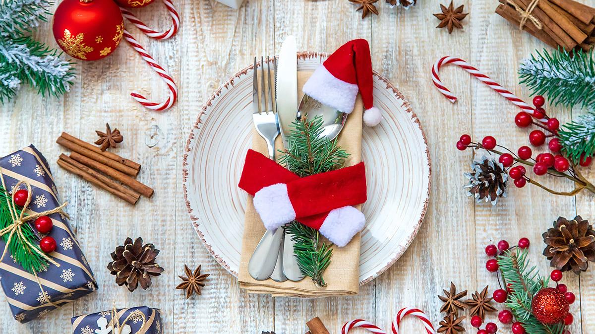 Une vaisselle de Noël traditionnel avec assiette rouge et blanc et des couverts en argent